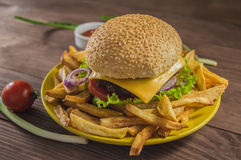 Big sandwich - hamburger burger with beef, cheese, tomato. On a wooden rustic background. Close-up Royalty Free Stock Image