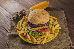 Big sandwich - hamburger burger with beef, cheese, tomato. On a wooden rustic background. Close-up Stock Photo