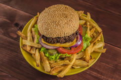 Big sandwich - hamburger burger with beef, cheese, tomato. On a wooden rustic background. Close-up Royalty Free Stock Photos