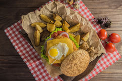Big sandwich - hamburger burger with beef, cheese, tomato.On a wooden rustic background. Top view. Close-up Royalty Free Stock Photos