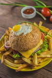 Big sandwich - hamburger burger with beef, cheese, tomato.On a wooden rustic background. Top view. Close-up Stock Photos