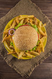 Big sandwich - hamburger burger with beef, cheese, tomato.On a wooden rustic background. Top view. Close-up Royalty Free Stock Images