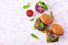 Big sandwich - hamburger burger with beef, pickles, tomato and red onions on a light background. Stock Photos