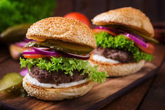 Big sandwich - hamburger burger with beef, pickles, tomato and tartar sauce. Royalty Free Stock Photography