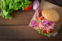 Big sandwich - hamburger burger with beef, red onion, tomato and fried bacon. Royalty Free Stock Image