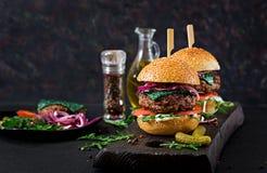 Big sandwich - hamburger burger with beef, tomato, basil cheese. And arugula stock photo
