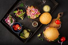 Big sandwich - hamburger burger with beef, tomato, pickled cucumber. And fried bacon. Flat lay. Top view stock photo