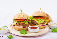 Big sandwich - hamburger with juicy beef burger, cheese, tomato, and red onion Royalty Free Stock Image