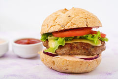 Big sandwich - hamburger with juicy beef burger, cheese, tomato, and red onion Stock Photography
