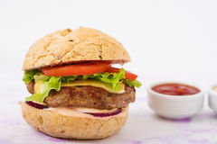 Big sandwich - hamburger with juicy beef burger, cheese, tomato, and red onion Stock Images