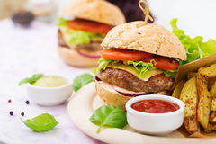 Big sandwich - hamburger with juicy beef burger, cheese, tomato, and red onion Stock Photos