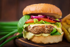 Big sandwich - hamburger with juicy beef burger, cheese, tomato, and red onion Stock Image