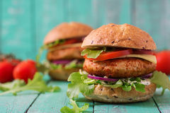 Big sandwich - hamburger with juicy chicken burger. Cheese, tomato, and red onion on wooden background stock photos