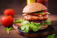 Big sandwich - hamburger with juicy chicken burger. Cheese, tomato, and red onion on wooden background royalty free stock photography