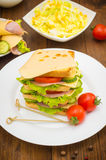 Big sandwich, meat, lettuce, cheese and vegetables on toasted. Wooden background. Close-up Royalty Free Stock Photos