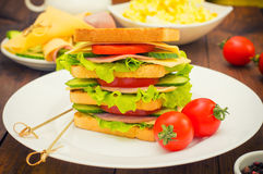Big sandwich, meat, lettuce, cheese and vegetables on toasted. Wooden background. Close-up Stock Photography
