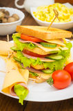 Big sandwich, meat, lettuce, cheese and vegetables on toasted. Wooden background. Close-up Stock Photos