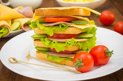 Big sandwich, meat, lettuce, cheese and vegetables on toasted. Wooden background. Close-up Stock Image