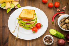 Big sandwich, meat, lettuce, cheese and vegetables on toasted. Wooden background. Top view. Close-up Royalty Free Stock Photo