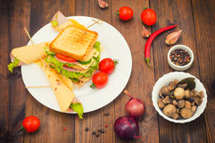 Big sandwich, meat, lettuce, cheese and vegetables on toasted. Wooden background. Top view. Close-up stock photo