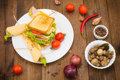 Big sandwich, meat, lettuce, cheese and vegetables on toasted. Wooden background. Top view. Close-up Stock Photos