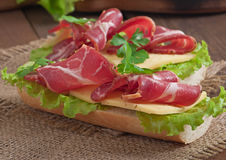 Big sandwich with raw smoked meat Royalty Free Stock Photo