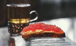 Big sandwich with red caviar and tea. Selective focus. Close up stock images