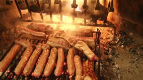 Big sausages cooked on the hot coals of fireplace stock footage