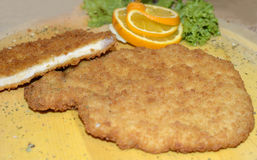 Big Schnitzel, roast meat. Served fresh roast pork meat on a wooden plate with garnish. Its a typical and traditional German meal called as Schnitzel. Delicious stock photo