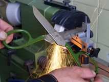 Scissors sharpening in the workshop,workers hands,sparkles. Big scissors sharpening in the workshop, workers hands,sparkles stock images