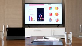 Big screen plasma TV that displays company sales report in empty conference room. Before the meeting starts. Dolly close up footage stock video
