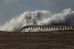 Big sea wave crashing against a pier Stock Photos