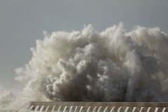 Big sea wave crashing against a pier Stock Images