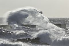 Big sea wave splash. Soft backlit. New pier and beacon from the Douro river mouth, Porto, Portugal Stock Photography