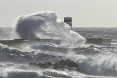 Big sea wave splash. Soft backlit. New pier and beacon from the Douro river mouth, Porto, Portugal Stock Images