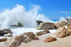 Big sea wave splashing over the shore rocks. With a high sea spray Royalty Free Stock Photography