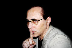 Big secret. The man presses an index finger to lips stock photography