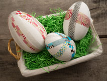 Big selfmade easter eggs in a basket with easter grass. Three selfmade easter eggs with colored taped on a wooden table with easter grass Stock Photos