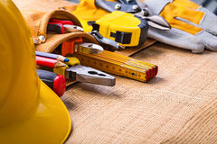 Big set of construction tools in toolbelt hardhat. Screwdriver pencil nippers pliers  wrench tape measure cutter gloves on wooden board Royalty Free Stock Image