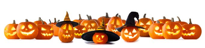 Big set of Halloween pumpkins. Big collection of Jack O Lantern Halloween pumpkins with various different designs and witches hat in a row isolated on white royalty free stock image