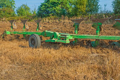 Big set of plough on field in work agricultural Royalty Free Stock Image