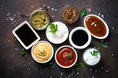 Big set of sauces. Set of sauces - ketchup, mayonnaise, mustard soy sauce, bbq sauce, pesto, mustard grains and pomegranate sauce on dark rusty stone or metal royalty free stock photo