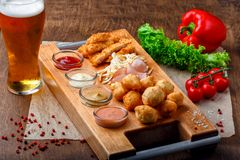 Big set of snacks for beer it includes fried cheese balls, pigtail cheese, ham and crab sticks on a wooden board stock photos