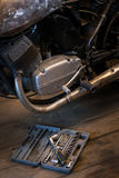 Big set tools, wich lying near engine of motorcycle in garage Royalty Free Stock Image