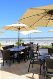 Big shade umbrellas over dining tables on outdoor patio at the beach Royalty Free Stock Photos