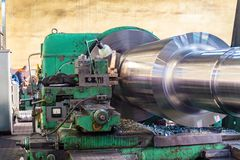 The big shaft is made on a huge lathe in the workshop royalty free stock image