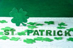 Big shamrock and the words St Patrick. Saint Patrick words spelled with green wooden letters and a big green shamrock in the back, surrounded by paper clovers Royalty Free Stock Images
