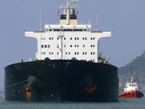 Big Ship. Large bulk cargo ship arriving at Port assisted by tugboat Stock Photos