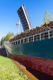 Big ship with a cargo of wood comes to the lock Stock Photography