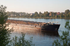 A big ship carrying wood. Ship transporting rows of logs Stock Photo